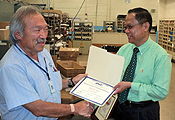 Ron Fujii (left) receives a Retirement Commendation from APWU San Jose Area Local president Ed Peralta. The 42-year postal veteran is now a member of the union's Retiree Department.